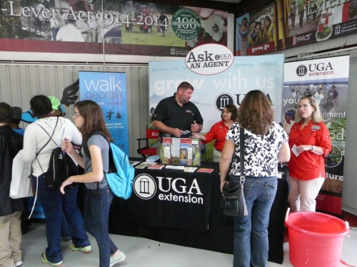 County Agents Brock Ward (Miller County), Stephanie Benton (Early County) and Melinda Miller (4-H PDC) talk with folks inside UGA Building